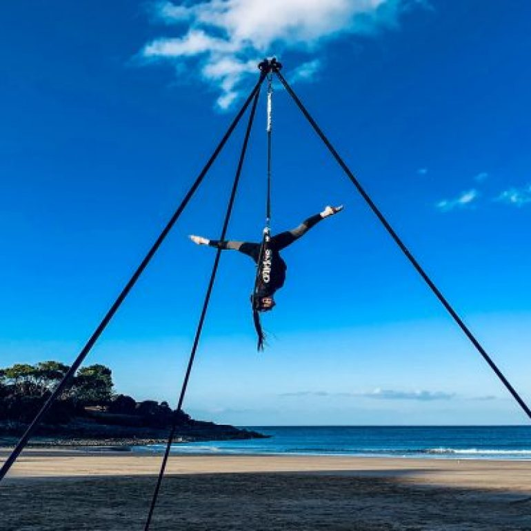 An acrobat hangs from a triangular frame whilst doing the splits upside down on a beautifully sunny day.