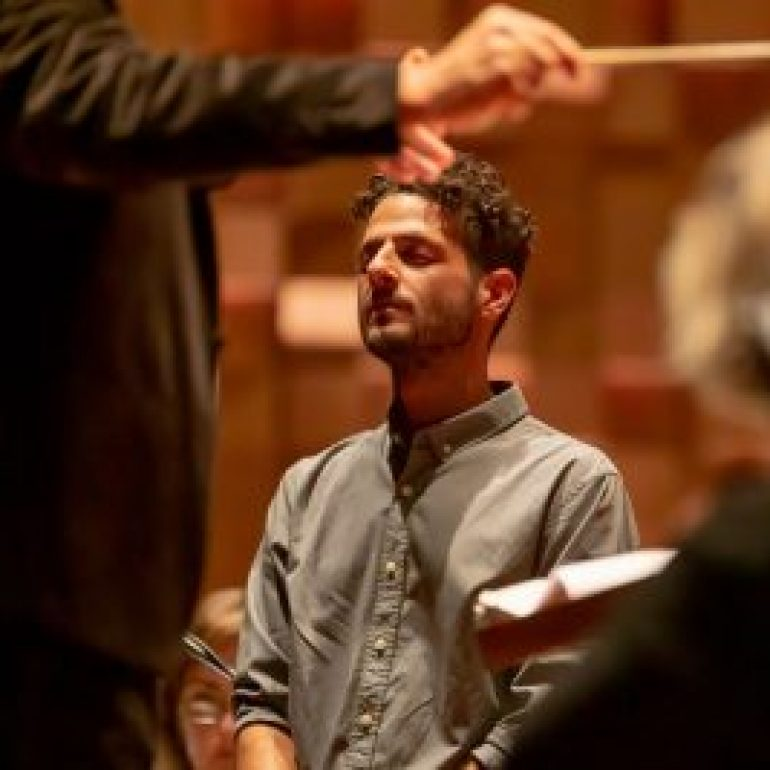 An image of a man with his eyes closed in front of a conductor, he is a member of the performance